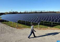 Un technicien passe près de panneaux solaires sur le site de la première centrale solaire photovoltaïque au sol en France métropolitaine, le 19 novembre 2008 à Lunel. Le site qui s'étend sur 1,5 hectares, permet l'implantation de plus de 6500 modules photovoltaïques qui convertissent de l'énergie lumineuse en énergie électrique. La production de la centrale sera de 605 900 kWh électrique par an. L'intégralité de la production sera injecté sur le réseau de distribution national, sur la ligne haute tension (20000 volts) souterraine qui borde le site. AFP PHOTO PASCAL GUYOT / AFP PHOTO / PASCAL GUYOT
