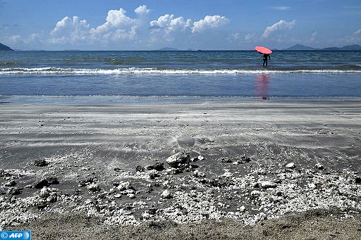 A surfer wades into the water as bits of palm oil (bottom) is seen on the sand of a beach in Hong Kong on August 7, 2017. Ten beaches typically packed on a hot weekend were closed in Hong Kong on August 6 due to a palm oil spillage from a ship collision in mainland Chinese waters. / AFP PHOTO / Anthony WALLACE