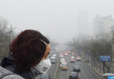 A woman wears a face mask on a heavily polluted day in Beijing on December 26, 2015. Thick smog continued a day after Beijing residents woke up to a white Christmas on December 25 with the sky obscured by thick toxic smog rather than snow. AFP PHOTO / GREG BAKER / AFP PHOTO / GREG BAKER