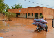 A man rides a motorbike with his belongings in a flooded street of Niamey following heavy rains, on June 15, 2017. At least nine children have been killed in Niger as heavy rains over the past few days caused the collapse of houses in the capital Niamey, the authorities said on June 14, 2017.  / AFP PHOTO / BOUREIMA HAMA