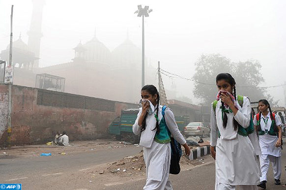 Indian schoolchildren cover their faces as they walk to school amid heavy smog in New Delhi on November 8, 2017. Delhi shut all primary schools on November 8 as pollution levels hit nearly 30 times the World Health Organization safe level, prompting doctors in the Indian capital to warn of a public health emergency. Dense grey smog shrouded the roads of the world's most polluted capital, where many pedestrians and bikers wore masks or covered their mouths with handkerchiefs and scarves.  / AFP PHOTO / SAJJAD HUSSAIN