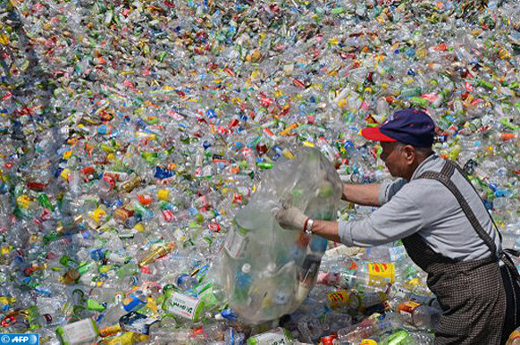 In a picture taken on February 28, 2013, a volunteer of the Taiwan Buddhist Tzu Chi Foundation sorts through plastic bottles at a recycling plant in Taipei.  Some 40 people stand ankle-deep in used plastic bottles in the yard of a recycling station in Taipei, stamping them flat in the first step of a process that will transform the junk into usable goods.  AFP / Sam YEH / AFP PHOTO / SAM YEH