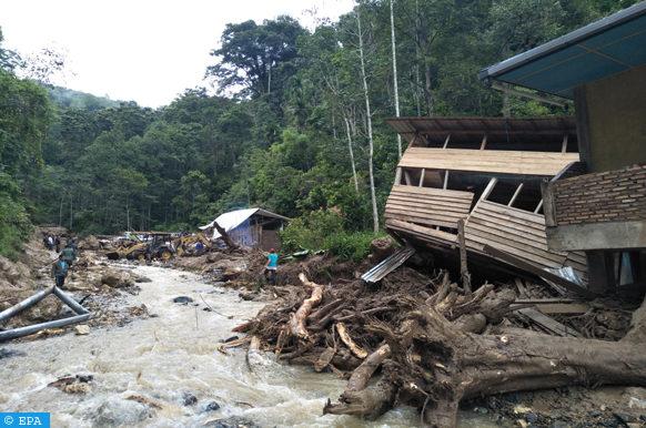 epa07090366 Indonesian people inspect the ruins of damaged buildings after a flash flood hit Muara Saladi Village, in Mandailing Natal, North Sumatra, Indonesia, 13 October 2018. According to media reports, a flash flood that hit North Sumatra killed at least 21 persons, injuring dozens.  EPA-EFE/AGUS SALIM