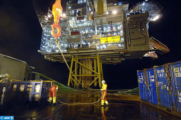 """POUR ILLUSTRER UNE SERIE DE TROIS PAPIERS SUR L'EXPLOITATION DU PETROLE OFFSHORE EN ANGOLA ET EN MER DE NORVEGE - Deux marins du remorqueur de haute-mer norvégien """"Bourbon Surf"""", travaillent, le 15 janvier 2007, au déchargement de matériel offhore au pied d'une plateforme pétrolière en mer de Norvège.  AFP PHOTO MARCEL MOCHET / AFP PHOTO / MARCEL MOCHET"""