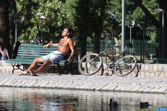 epa04004179 A man sits under the sun at the Centenario park in Buenos Aires, Argentina, 30 December 2013. According to media reports, at least six people died as a heat wave hit the country. A state of emergency has been declared due to power cuts and water shortages throughout Argentina.  EPA/SILVINA FRYDLEWSKY