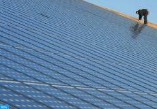 """Une personne travaille le 18 février 2008 à Weinbourg sur des panneaux d'un parc photovoltaïque, présenté comme la plus grande installation intégrée au monde avec ses 36.000 m² de panneaux faisant office de toiture.   Outre sa dimension qui va autoriser la production annuelle de 4,5 Mégawatts d'électricité, capable d'alimenter une ville de 4.000 habitants, la particularité de l'installation réside dans le fait que les panneaux ne sont pas posés sur un toit """"mais qu'ils sont le toit"""", a précisé mercredi à l'AFP M. Westphal, agriculteur à l'origine du projet.     AFP PHOTO/ FREDERICK FLORIN  A worker installs solar panels on a 36,000 square meters solar panel installation, the largest in the world, spread over five hangars at a farm, used as a giant roof in Weinbourg, Eastern France on February 18, 2009. The solar panels will yield 4,5 Megawwats a year, which will enable to provide energy for a city of 4,000, said Mr Westphal, a farmer who is behind the project. AFP PHOTO/ FREDERICK FLORIN (Photo by FREDERICK FLORIN / AFP)"""